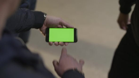 Thumbnail for of Young Male Hands Holding Modern Smartphone with Green Touch Screen. Man's Hand Shows Mobile