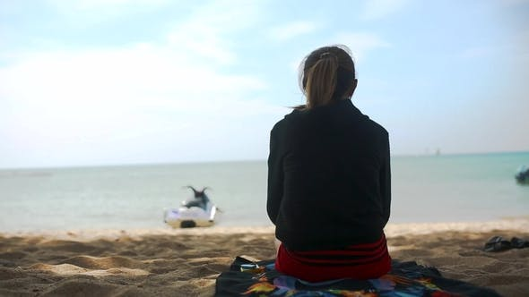 Thumbnail for Rear View of a Girl in a Hoodie Sitting on the Beach and Watch the Sea, Blue Sky and Sea Background