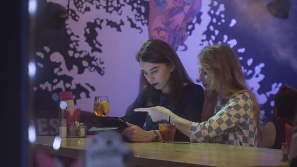 Thumbnail for Two Beautiful Young Women Sitting at Cafe and Looking at Digital Tablet Teamwork, Two Young