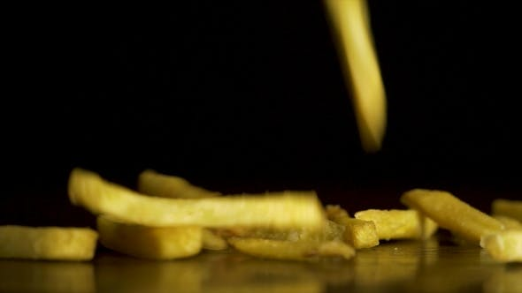Thumbnail for French Fries Fall on the Table Isolated on Black Background. Fastfood. French Fries. Flying Fried