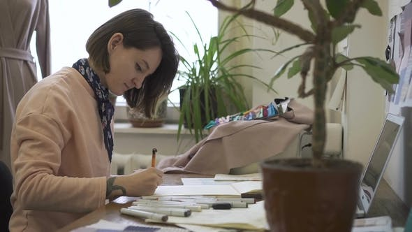 Thumbnail for Portrait of Female Fashion Designer, Who Is Working on the Sketch of New Model in Her Bright Studio