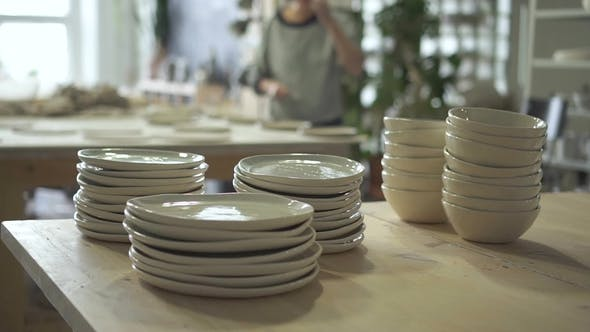 Thumbnail for Stacks of Plates and Bowls, Which Are Standing on Wooden Table in Bright Ceramic Studio