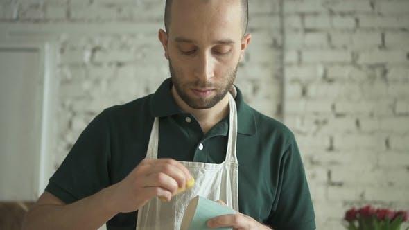 Thumbnail for Portrait of Male Ceramist, Who Is Sponging Mug Bottom in Ceramic Studio.