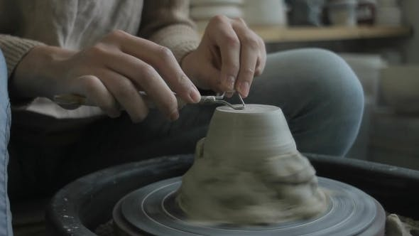 Thumbnail for Young Ceramist is Polishing Clay Vase While Sitting in Modern Workshop