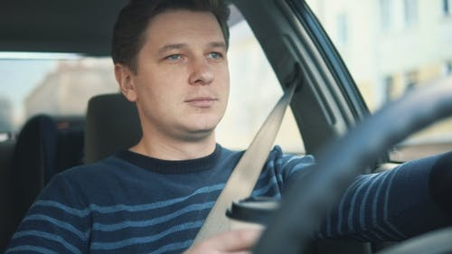A Young Attractive Man Is Drinking Coffee in Car