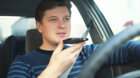 Thumbnail for A Young Attractive Man Is Using a Mobile Phone on the Speakerphone in the Car