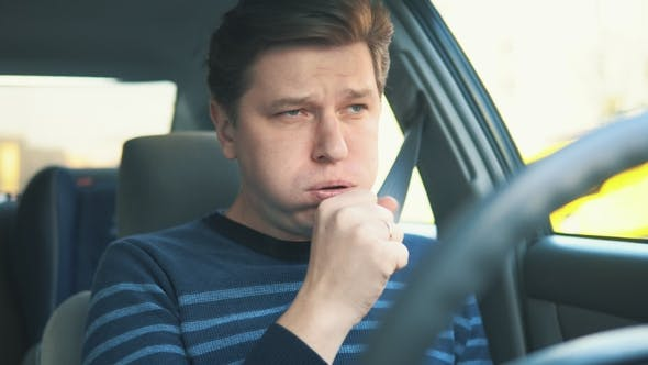 Thumbnail for A Young Attractive Man Is Coughing While Driving in Car
