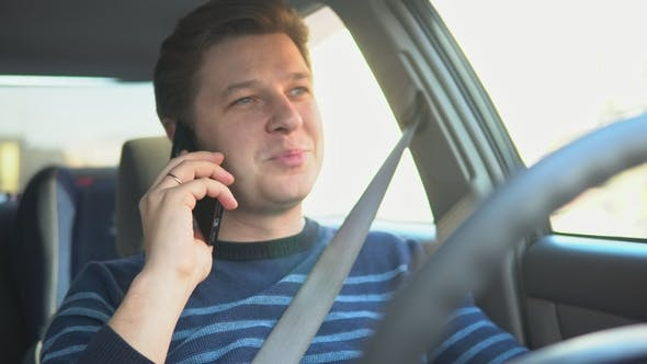 Cover Image for A Young Attractive Man Is Talking in the Car on the Phone and Drinking Coffee