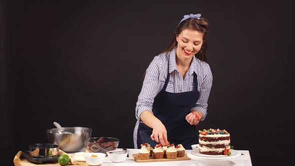 Cover Image for Confectioner Woman Is Decorating Delicious Cake in Studio.
