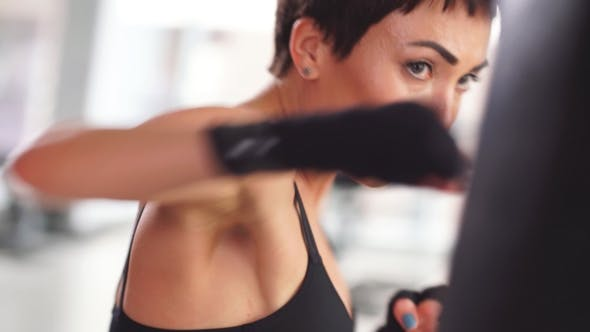Thumbnail for Attractive Female Boxer Training Punching a Heavy Bag in the Gym.