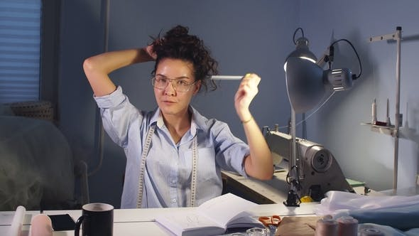 Female Tailor with Pencil in Mouth Putting Her Hair Back.