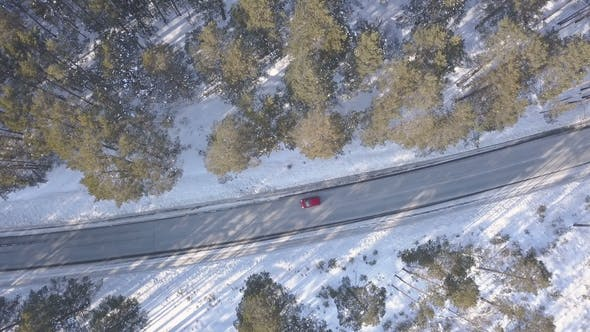 Thumbnail for Snowy Road with a Moving Red Car in Winter
