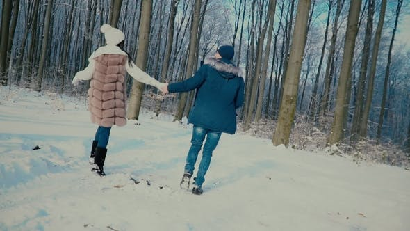 Couple Walking through the Winter Forest