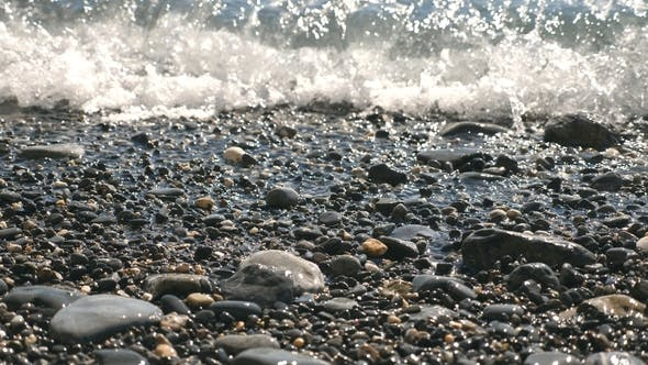 Cover Image for Calming Scene of Gentle Waves Splashing To Pebble Beach on Sunny Day