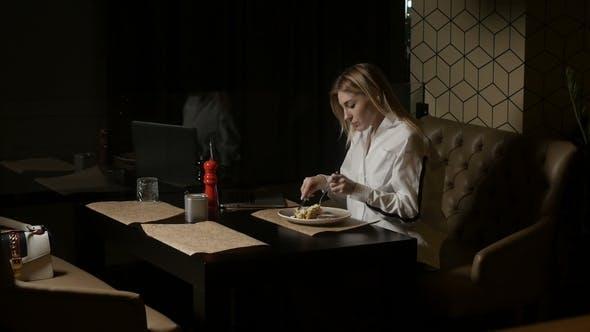 Frau mit Laptop hat Mittagessen