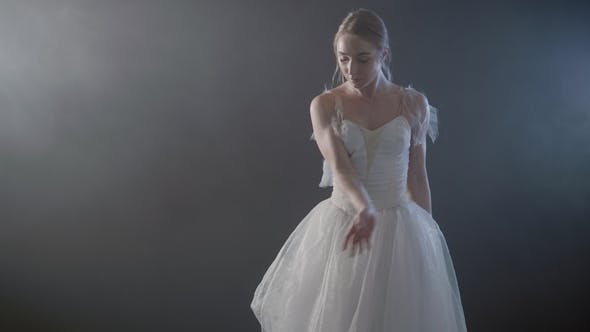 Thumbnail for Graceful Ballerina in White Tutu Dress Dancing Elements of Classical or Modern Ballet in the Dark