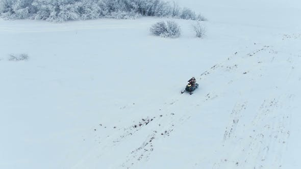 Thumbnail for Aerial. A Snowmobile Is Riding Through the Snow