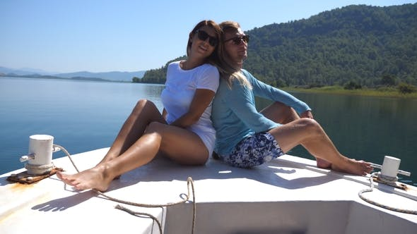 Thumbnail for Young Pair Sitting Back To Back and Posing on Bow of Boat at Sunny Day Happy Couple in Love