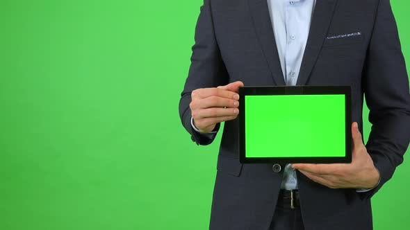 Thumbnail for A Businessman in a Suit Holds Out a Tablet with Green Screen - Closeup - Green Screen Studio