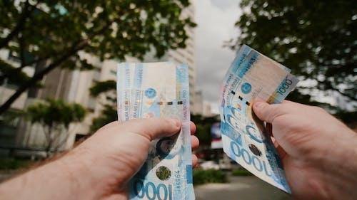 The Man Recounts the Filipino Money Bills. Thousand Bills.