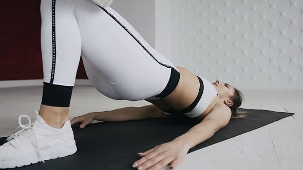 Thumbnail for Sexy Fitness Athlete Dressed in White Sportswear Performs an Exercise Bridge on the Mat at Gym In