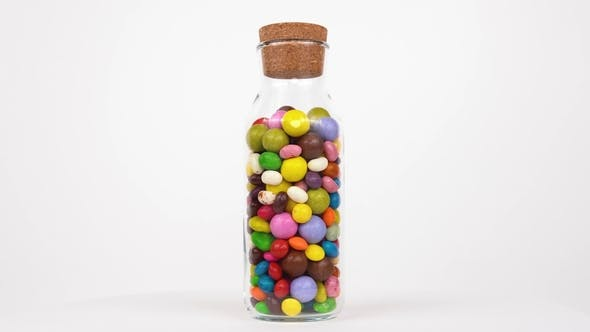 Thumbnail for Variety of Colored Candies Rotate in a Transparent Bottle on White Background. Isolated. Loopable.