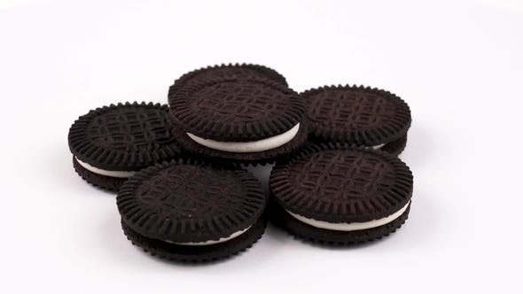 Thumbnail for Chocolate Sandwich Cookies with White Cream Isolated on White Background. Rotating on a Turn Table
