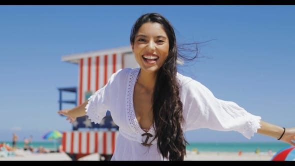 Thumbnail for Cheerful Ethnic Woman Laughing on Beach