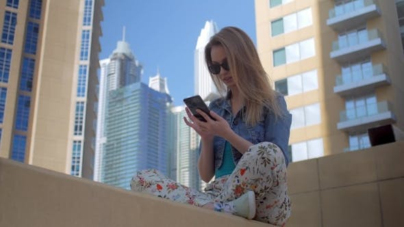 Thumbnail for Teenage Girl Is Using Smartphone Sitting in Background of Modern Skyscrapers