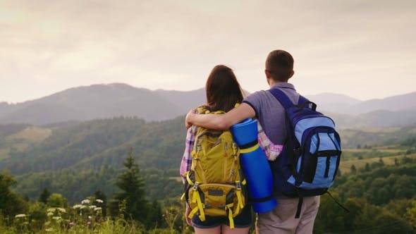 Thumbnail for A Young Couple of Travelers Looking Forward To the Horizon and Mountains