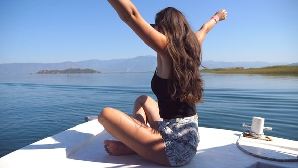 Thumbnail for Young girl sitting on bow of boat, looking to beautiful landscape and raising hands to enjoy freedom