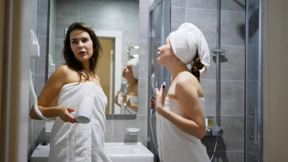Thumbnail for Girl in White Towels Sing Into Comb and Dance in Front of Mirror