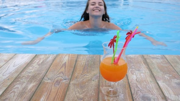 Cover Image for Girl in Bikini on Swimming-pool Edge on Hot Sunny Day Enjoys Colorful Beverage Summer Rest