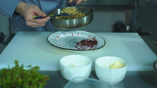 der Chefkoch serviert einen Teller Sauce