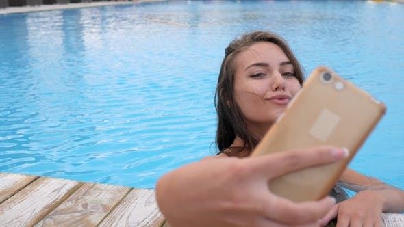 Thumbnail for Girl in Swimsuit Makes Photo with Colorful Beverage on Swimming-pool Edge