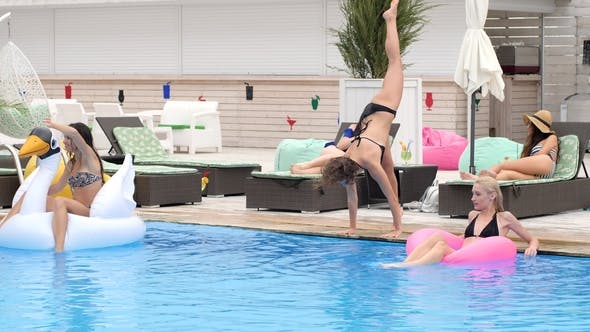 Cover Image for Summer Party Girl in Swimsuit Makes Beautiful Jump into Blue Pool on Background Group People