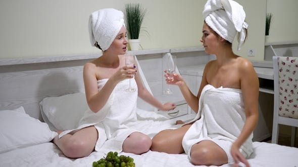 Cover Image for Party of Friends Girls Wrapped in a Towels Drink Champagne and Chatting on the Bed in Bedroom