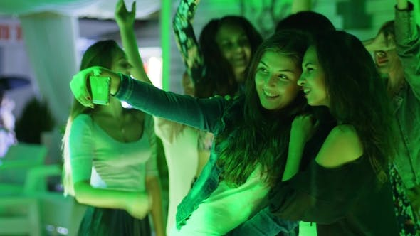 Cover Image for Selfi Photo Friends Close Together Makes Pictures on Smartphone at Party in Nightclub