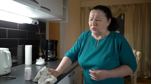 Senior Woman Suffering From Stomach Ache at Home and Takes the Pills