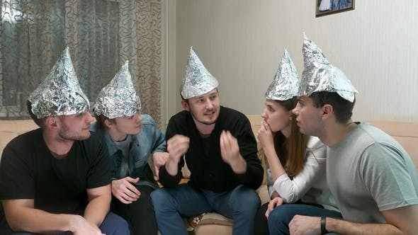 Thumbnail for Group of People with Foil on Their Heads Discussing Conspiracy Theories. Friends with Foil on Their