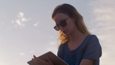 Woman Is Using Tablet, Static Shot on Background of Evening Sky