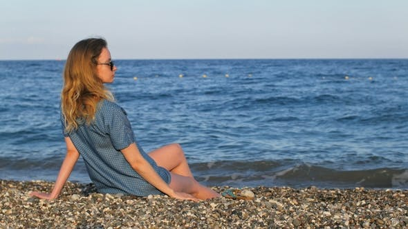 Thumbnail for Lonely Slim Blonde Sitting on a Pebble Beach in Front of Sea in Profile, Then Touching Hair