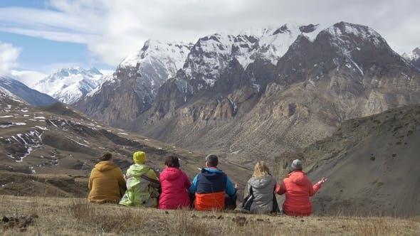 Thumbnail for Wanderer lehnen sich zurück und schauen Sie sich das Bergtal an