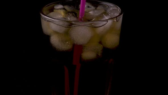 Thumbnail for Woman Stirs a Cold Drink with a Cocktail Straw on a Black Background