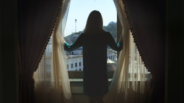 Thumbnail for Young Woman Walking To Window and Opening Curtains Back View