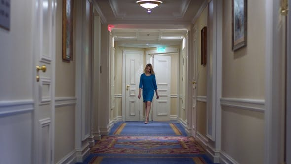 Thumbnail for Beautiful Woman in Blue Dress Walking Along Corridor at Luxury Mansion