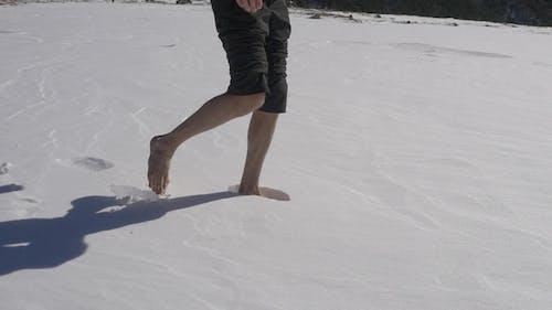 Man Walks on Fresh Untouched Snow Barefoot