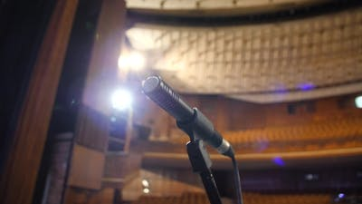 Microphone on Stage in Concert Hall or Conference Ball Room. Microphone on Stage with Shiny Rays