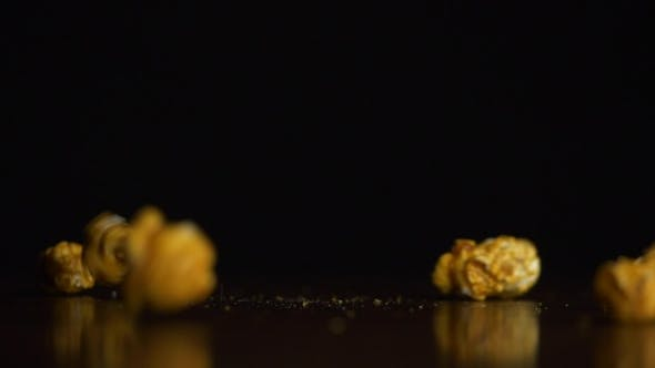 Yellow Fluffy Pieces of Popcorn Fall in  Against a Black Background and Bounce