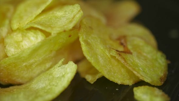Thumbnail for Potato Chips Rotating On Black Background. Potato Chips Are Rotated on a Black Background.  of Yello